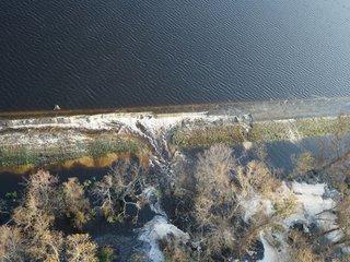Floodwaters breach power plant's dam